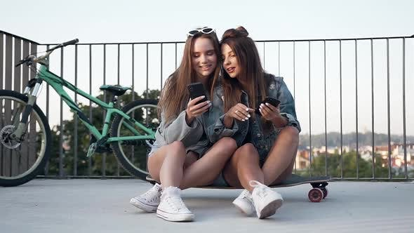 Thumbnail for Girlfriends Sitting on the Skateboard and Having fun During Watching Photos