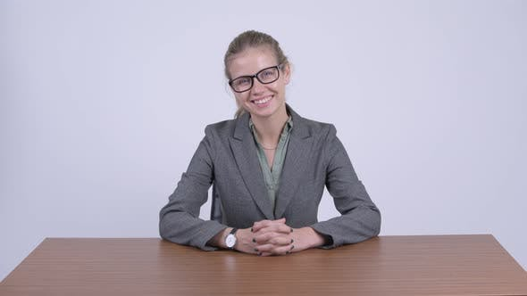 Thumbnail for Young Happy Blonde Businesswoman Smiling and Sitting Behind Desk