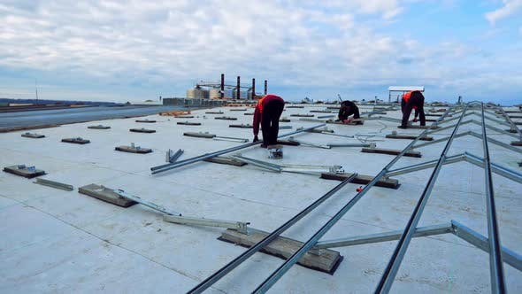 Thumbnail for Workers install metal base for solar panels