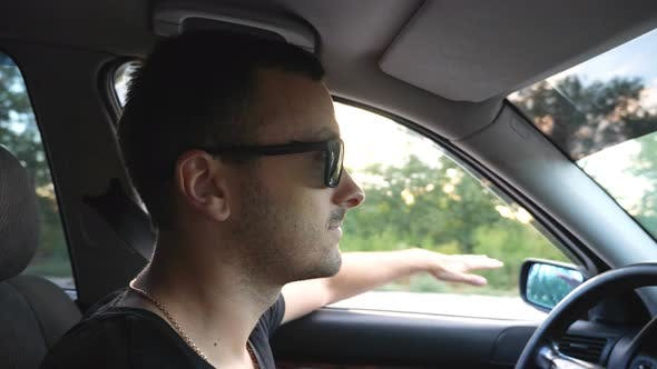 Profile of Handsome Man in Sunglasses Driving Car at Countryside