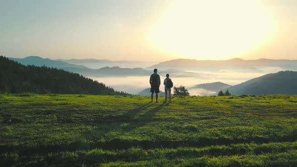 A Man and a Woman on Top of a Mountain Meet the Sunrise