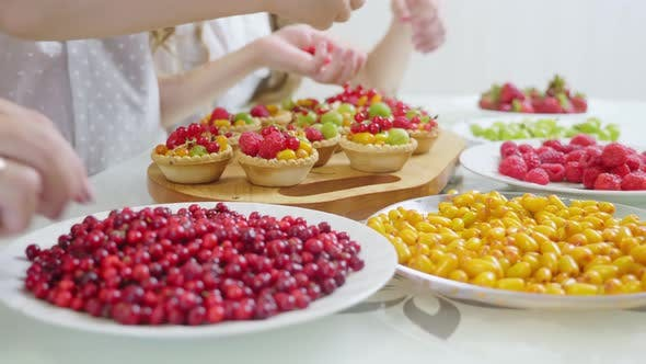 Thumbnail for In the Kitchen Concept The Family Decorates the Pie and Muffins with a Berry