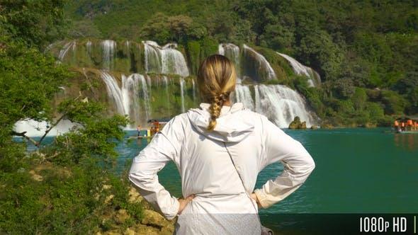 Thumbnail for Raising Above a Woman Looking at a Waterfall