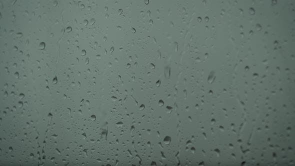 Close Up of a Glass with Water Drops While Outside Is Raining. Drops of Rain Through Glass.