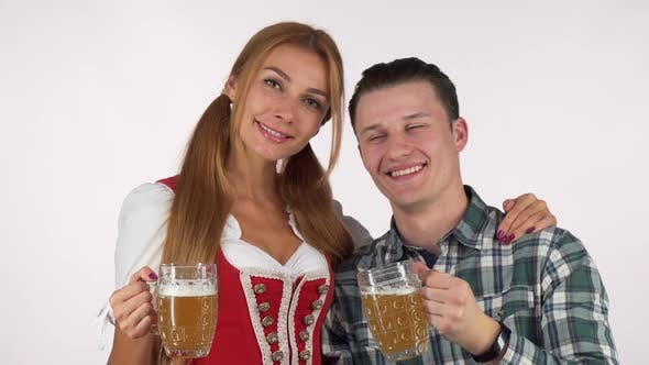 Thumbnail for Happy Oktoberfest Couple Clinking Beer Mugs, Smiling at Each Other