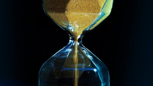 Cover Image for Close up of hourglass with falling golden grains