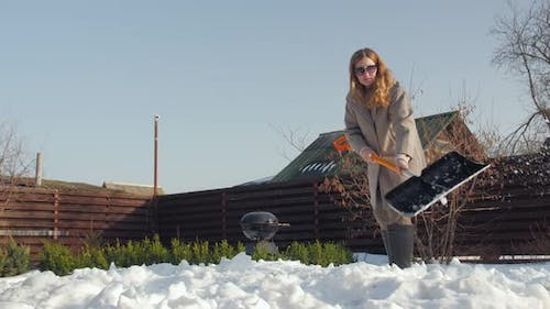 Woman Cleans Snow In Yard