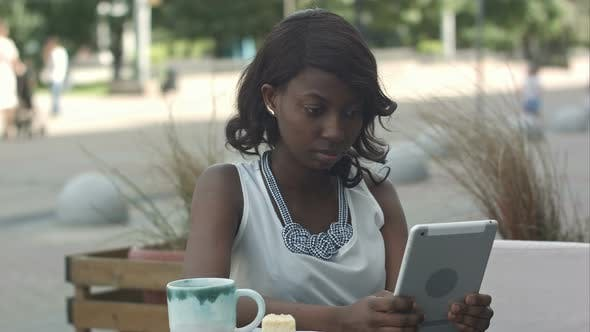 Thumbnail for African Young Business Woman Working and Using Tablet in Outdoor Cafe