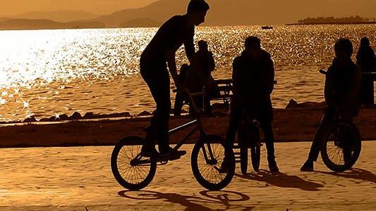 Thumbnail for Freunde mit Fahrrädern bei Sonnenuntergang