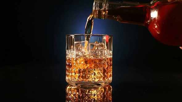 Thumbnail for Bottle Pours Whiskey Into A Glass With Ice Cubes