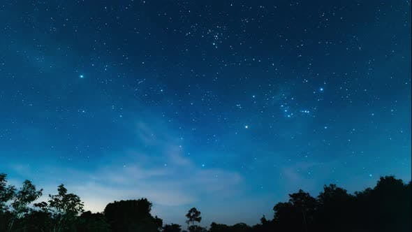 Starry night in mountains Time lapse. Milky way galaxy stars moving over countryside traffic