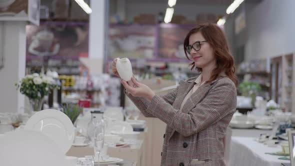 Beautiful Shopper with Glasses for Female Vision Chooses Crockery for Set of Dishes in Department