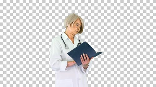 Mature woman doctor with a stethoscope reading log, Alpha Channel