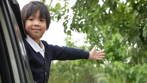 Happy Asian Boy Travels By Car