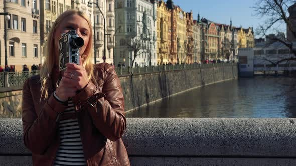 Thumbnail for A Young Attractive Woman Shoots a Video with a Camera - a River and Buildings of a Quaint Street