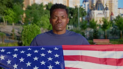Camera Zoom in Patriot AfroAmerican Man Holding American Flag and Looks Camera