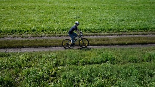 Thumbnail for Man Cycling On a Rural Road. Aerial View.