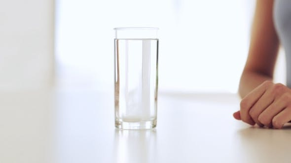 Thumbnail for Woman Dissolving Pill In Water Glass