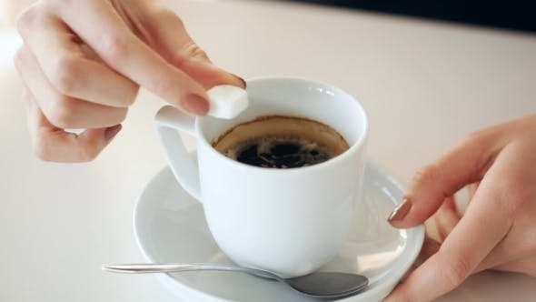 Thumbnail for Woman Hands Adding Sugar To Coffee Cup