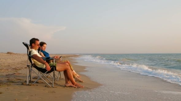 Thumbnail for Romantic Couple Relaxing On Loungers At Beach