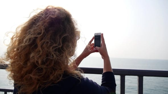 Thumbnail for Woman Taking Pictures Of Sea With Smartphone