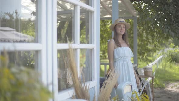 Thumbnail for Adorable Young Smiling Woman in Straw Hat and Long White Dress Looking Away in Front of the Small