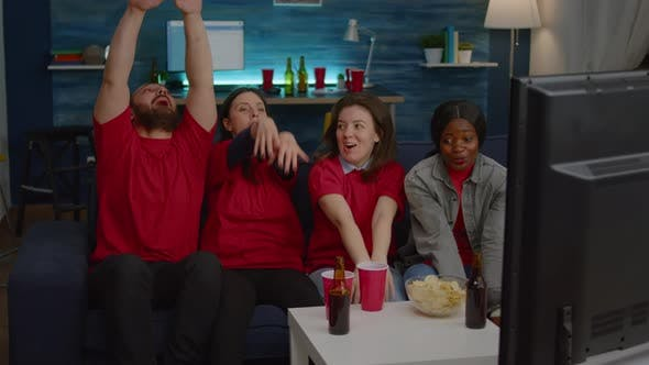 Multiethnic Friends Sitting on Couch in Front of Tv Watching Football Cheering Team Goal