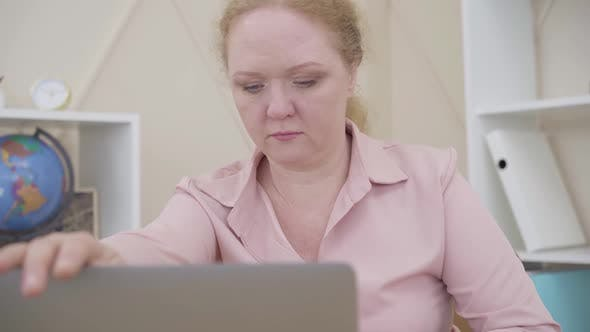 Senior Redhead Woman Closing Laptop and Looking at Camera. Lady Expressing Opposite Emotions