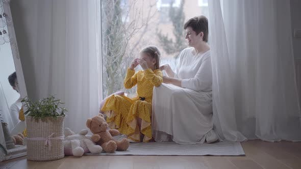 Thumbnail for Pretty Positive Girl Playing with Toy As Grandmother Tying Her Hair in Ponytails. Happy Caucasian