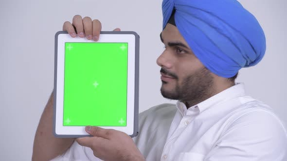 Thumbnail for Face of Happy Young Bearded Indian Sikh Man Showing Digital Tablet