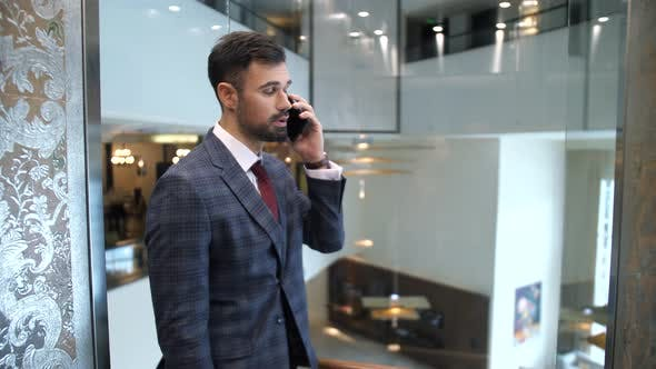 Handsome Man Talking on Phone in Elevator
