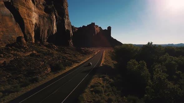 Thumbnail for Drone Camera Follows Car Driving Along Small Desert Highway Road Near Breathtaking Steep Canyon