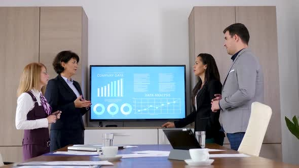 Thumbnail for Business Team in Conference Room Beside a Big Screen TV