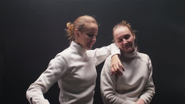 Cover Image for Two Young Women Fencers Fooling Around with a Sword When Posing for the Camera