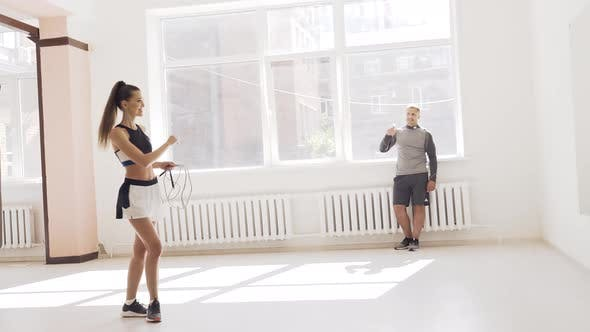 Thumbnail for In a Bright Gym with Large Windows a Young Female Athlete Jumps on a Rope Under the Supervision of a