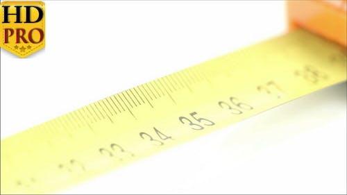Ein orangefarbenes Maßband mit gelben Zahlen