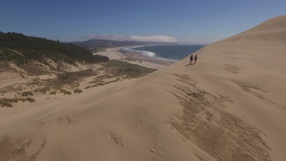 Thumbnail for Aerial view of couple hiking on sand dunes at beach