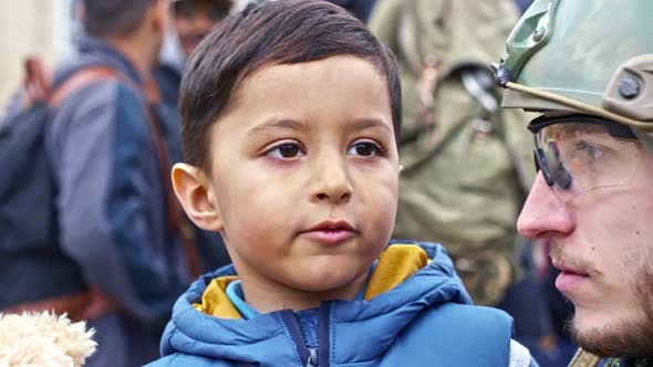 Cover Image for Little Refugee Boy Talking with Soldier