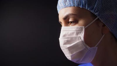 Female Doctor or Nurse in Face Mask Praying