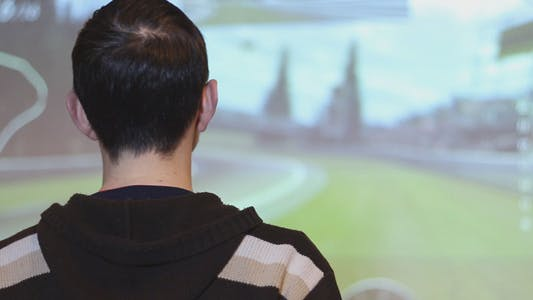 Cover Image for Boy Playing on the Console to the Big Screen