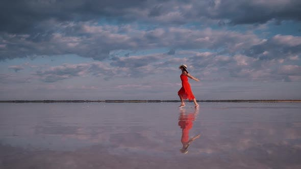 Thumbnail for Girl in a Fluttering Dress Runs Along a Salt Lake. Clouds Are Reflected in the Water