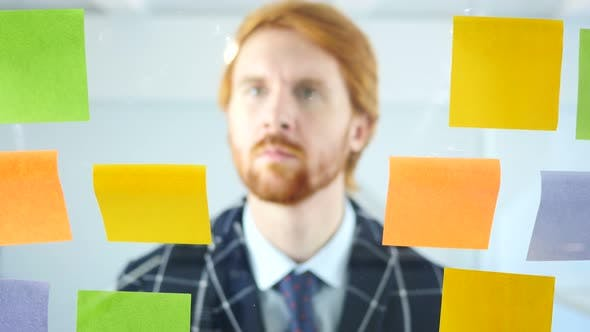 Thumbnail for Redhead Businessman Working On Sticky Notes Attached on Glass