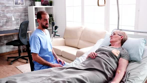 Caucasian Doctor in Nursing Home Talking with Old Woman