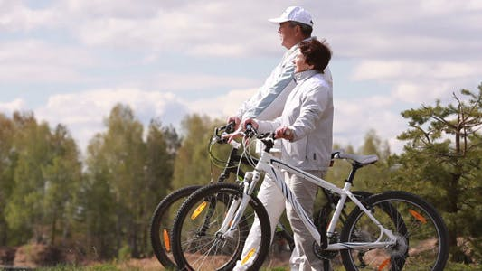 Thumbnail for Talking senior couple with bicycles