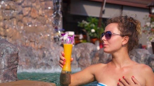 Cover Image for Junge Frau trinken Fruchtsaft im Schwimmbad