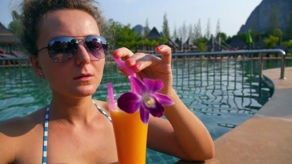 Thumbnail for Girl Drinking Fresh Mango Juice In Luxury Pool On