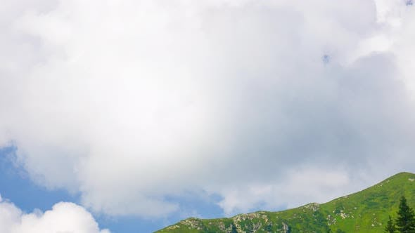 Thumbnail for White Clouds Fly Over Mountain with Green Grass at Blue Sky Background