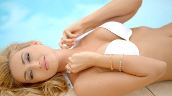 Thumbnail for Frau in weiß Bikini liegend neben Pool