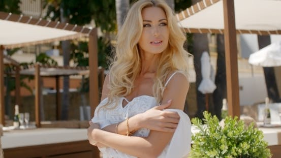 Thumbnail for Blond Woman Wearing White Peasant Blouse At Resort
