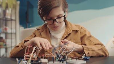 Caucasian Schoolboy Constructing Robot